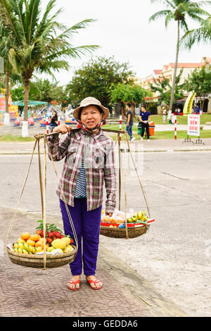 Hoi An, Vietnam - February 16, 2016: Asian woman trader carrying fresh fruit in bowls on her shoulders in the street - Stock Photo