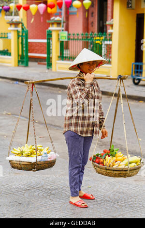 Hoi An, Vietnam - February 17, 2016: Asian woman seller carrying fresh fruit in bowls on her shoulders in the street - Stock Photo