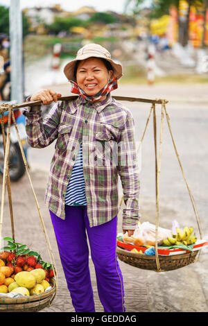 Hoi An, Vietnam - February 16, 2016: Asian woman seller carrying fresh fruit in bowls on her shoulders in the street - Stock Photo