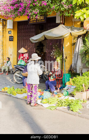 Hoi An, Vietnam - February 17, 2016: Asian woman selling bunches of fresh bananas in the street in Hoi An, Vietnam. - Stock Photo