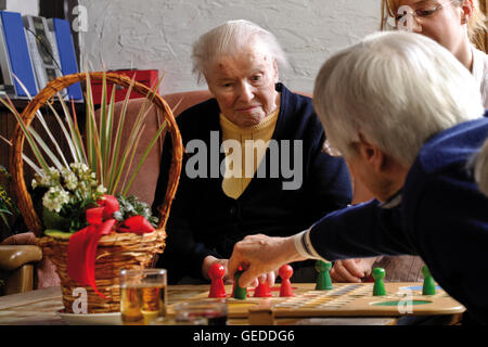Caregiver playing a board game with two elderly people at a nursing home - Stock Photo