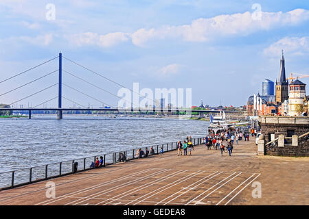 Dusseldorf, Germany - May 3, 2013: Rhine embankment promenade in the city center of Dusseldorf in Germany. Tourists nearby. It is the capital of Rhine Westphalia region. Stock Photo