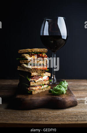 Caprese sandwich or panini and glass of red wine. Whole grain bread, mozzarella, dried tomatoes, basil. Dark background, - Stock Photo