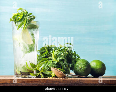 Homemade Mojito cocktail in tall glass with bunch of mint, brown sugar and limes - Stock Photo