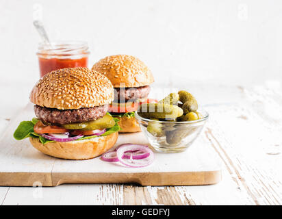 Two fresh homemade burgers, pickles, ketchup and onion rings on white wooden serving board - Stock Photo