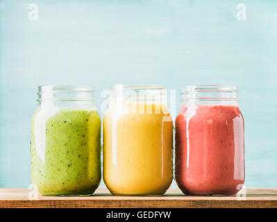 Fresh blended fruit smoothies of various colors and tastes in glass jars. Green, yellow, red. - Stock Photo