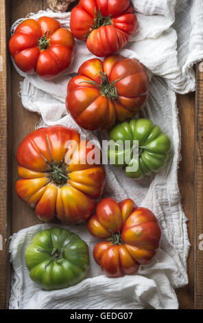 Colorful Heirloom tomatoes on white textile in rustic wooden tray, top view - Stock Photo