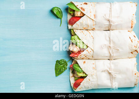 Healthy lunch snack. Three tortilla wraps with grilled chicken fillet and fresh vegetables over turquoise blue painted - Stock Photo
