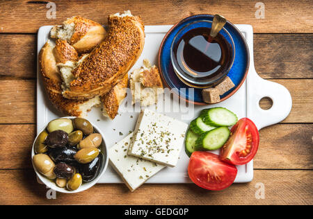 Turkish traditional breakfast with feta cheese, vegetables, olives, simit bagel and black tea on white ceramic board - Stock Photo
