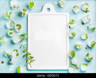 Ice cubes with frozen mint leaves inside on blue Turquoise background and white ceramic board in center, copy space - Stock Photo