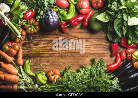 Fresh raw vegetable ingredients for healthy cooking or salad making over rustic wood background, top view, copy - Stock Photo