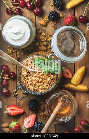 Healthy breakfast ingredients. Oat granola in open jar, yogurt and honey served with berries, nuts, fresh mint leaves - Stock Photo