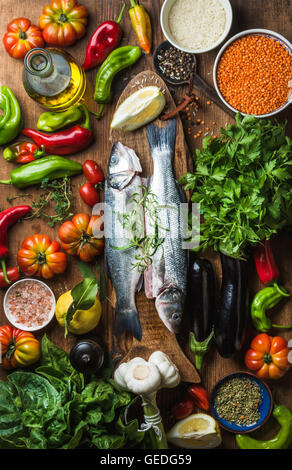 Raw uncooked seabass fish, vegetables, grains, herbs, rice spices and olive oil on rustic wooden chopping board, - Stock Photo