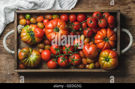 Colorful assortment of heirloom, bunch and cherry tomatoes in rustic tray over wooden background - Stock Photo