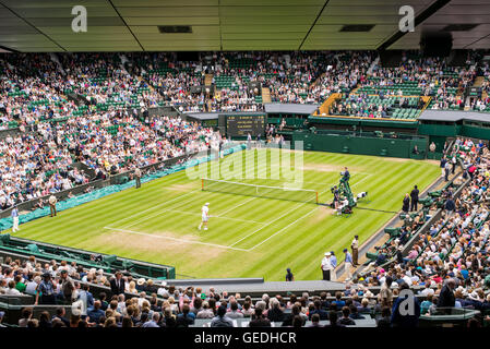 View of Centre Court full of spectators watching a game at Wimbledon All England Lawn Tennis Club Championships. - Stock Photo