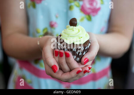 Close up shot of a woman's hands holding a brown cupcake topped with mint frosting. - Stock Photo