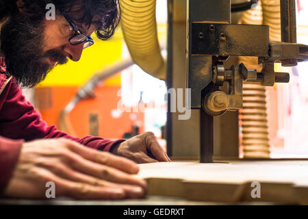 Woodworker Cutting Wood with Band saw - Stock Photo