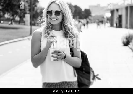 Black-and-white image of woman in sunglasses with drink - Stock Photo