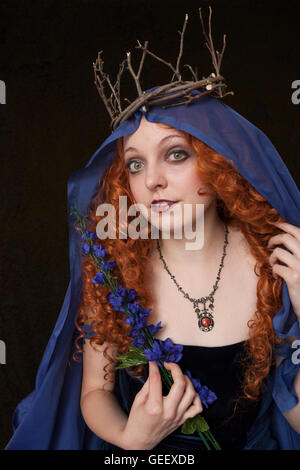 Beautiful young red haired woman wearing velvet blue dress and twig crown - Stock Photo