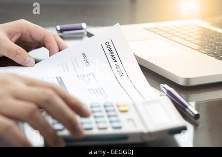 Business man review company invoice on his desk made a payment. laptop computer, pen and calculator. - Stock Photo