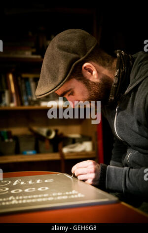 A sign writer working with a loaded brush painting a line freehand on the edge of a sign. - Stock Photo