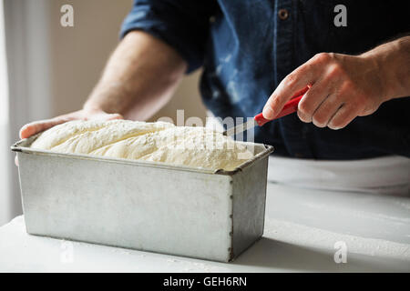 Close up of a baker cutting bread dough in a baking tin. - Stock Photo