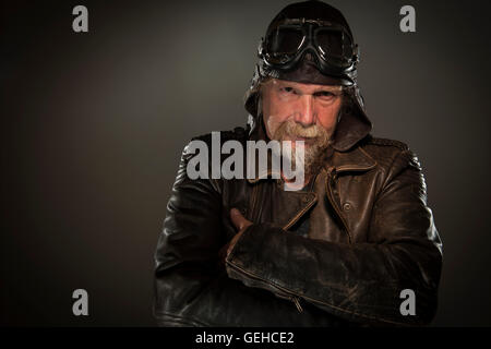frontal head and shoulders portrait of older man with a full beard, leather jacket and goggles seriously into the - Stock Photo