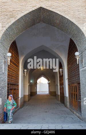 Uzbek woman in her traditional dress walks through the arched passageway in Bukhara, Uzbekistan. - Stock Photo