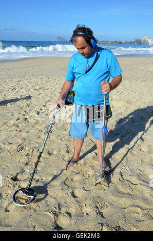 Rio de Janeiro, Brazil. 08th July, 2016. Carlos Saman uses a metal detector to look for objects tourists have lost - Stock Photo