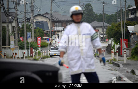 Tokyo, Japan. 26th July, 2016. A Japanese police officer can be seen directing traffic near Tsukui Yamayuri-en care - Stock Photo