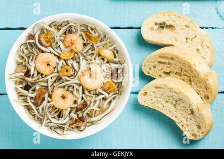 Surimi elvers with prawns, garlic and pepper on a white bowl, three slices of bread on a blue wooden table - Stock Photo