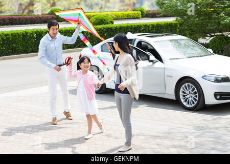 Happy young Chinese family flying a kite - Stock Photo