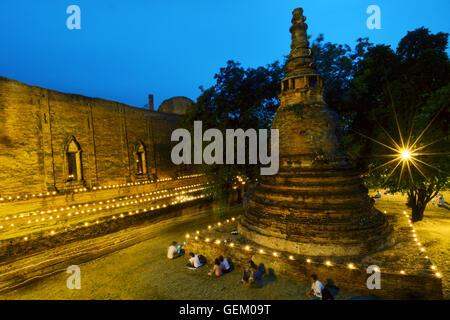 Candle light triple circumambulation activity around Buddha pagoda temple in Wat Maheyong Ayutthaya Thailand - Stock Photo