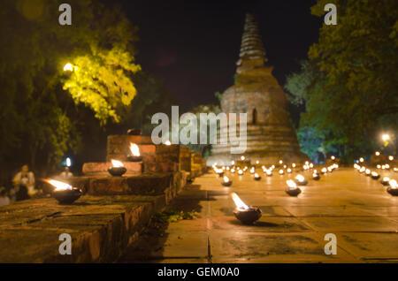 Series of candle light around Buddha pagoda temple in Wat Maheyong Ayutthaya Thailand - Stock Photo