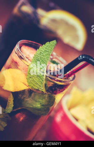 Glasses containing pimms drink and cola on a table in a pub - Stock Photo