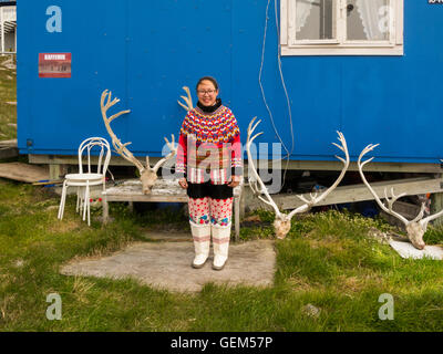 Young Inuit girl in Greenland traditional costume standing outside blue painted home Itilleq West Greenland with - Stock Photo