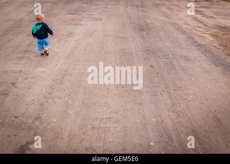 Little boy walking on a gravel, dusty and corrugated village road in the countryside - Stock Photo