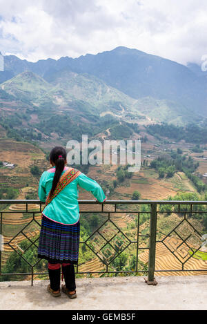 Vietnamese minority guide admiring the landscape with mountains and rice paddies in Sapa, North Vietnam. - Stock Photo