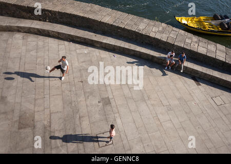 Aerial view of young men during a kickabout on the riverfront of the Douro in Porto, Portugal. - Stock Photo