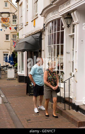 UK, England, Devon, Sidmouth, Old Fore Street, senior vistors looking into Antiques shop window - Stock Photo