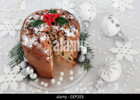 Chocolate panettone christmas cake with holly berries, white and silver snowflake and bauble decorations. - Stock Photo