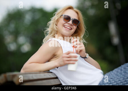 Laughing blond girl in sunglasses sitting on park bench - Stock Photo