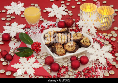 Christmas scene of Florentine biscuits on a heart shaped plate, eggnog, holly, candles and bauble decorations with - Stock Photo