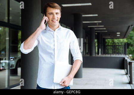 Cheerful young businessman holding laptop and talking on mobile phone near business center - Stock Photo