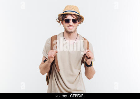 Portrait of cheeful happy young man with backpack over white background - Stock Photo