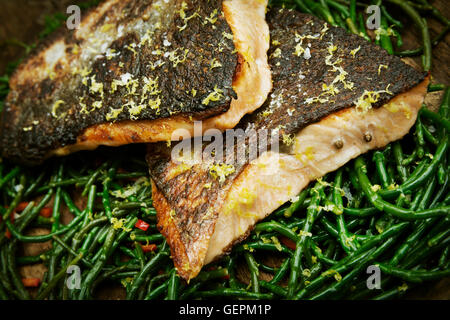 Close up of grilled fish fillets with crispy skin on a bed of samphire. - Stock Photo
