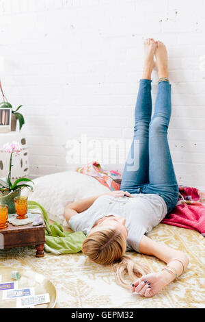 A young woman in jeans lyng on her back with her legs against the wall. - Stock Photo