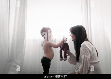 A heavily pregnant woman playing with her young son. - Stock Photo