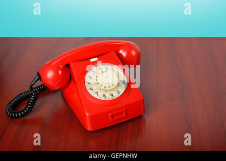 Vintage Phones - Red a retro telephone on a wooden table and a blue background. - Stock Photo