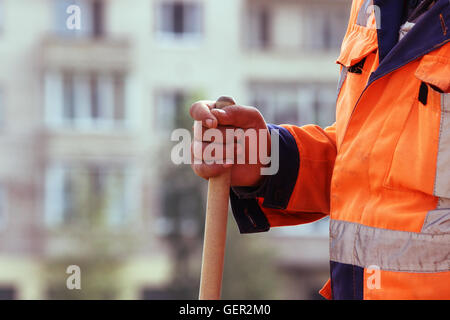 masons in the town square laid paving slabs. worker stands with a shovel. - Stock Photo